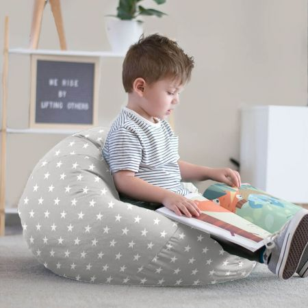 Little boy reading on small kids stars bean bag
